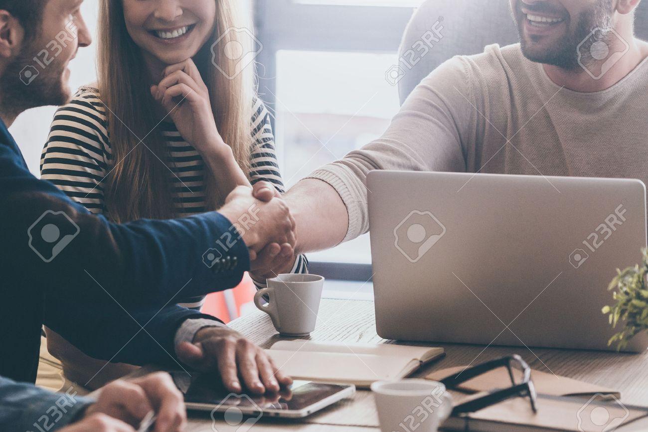 Bienvenue dans l'équipe! Close-up de deux jeunes hommes gais se serrant la main et en femme assise près d'eux et souriant Banque d'images - 58178137