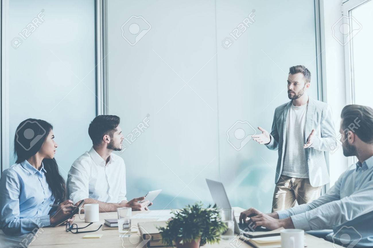 Arbre jeunes gens d'affaires assis au bureau de bureau tandis qu'un homme debout près d'eux et gestes Banque d'images - 59746322