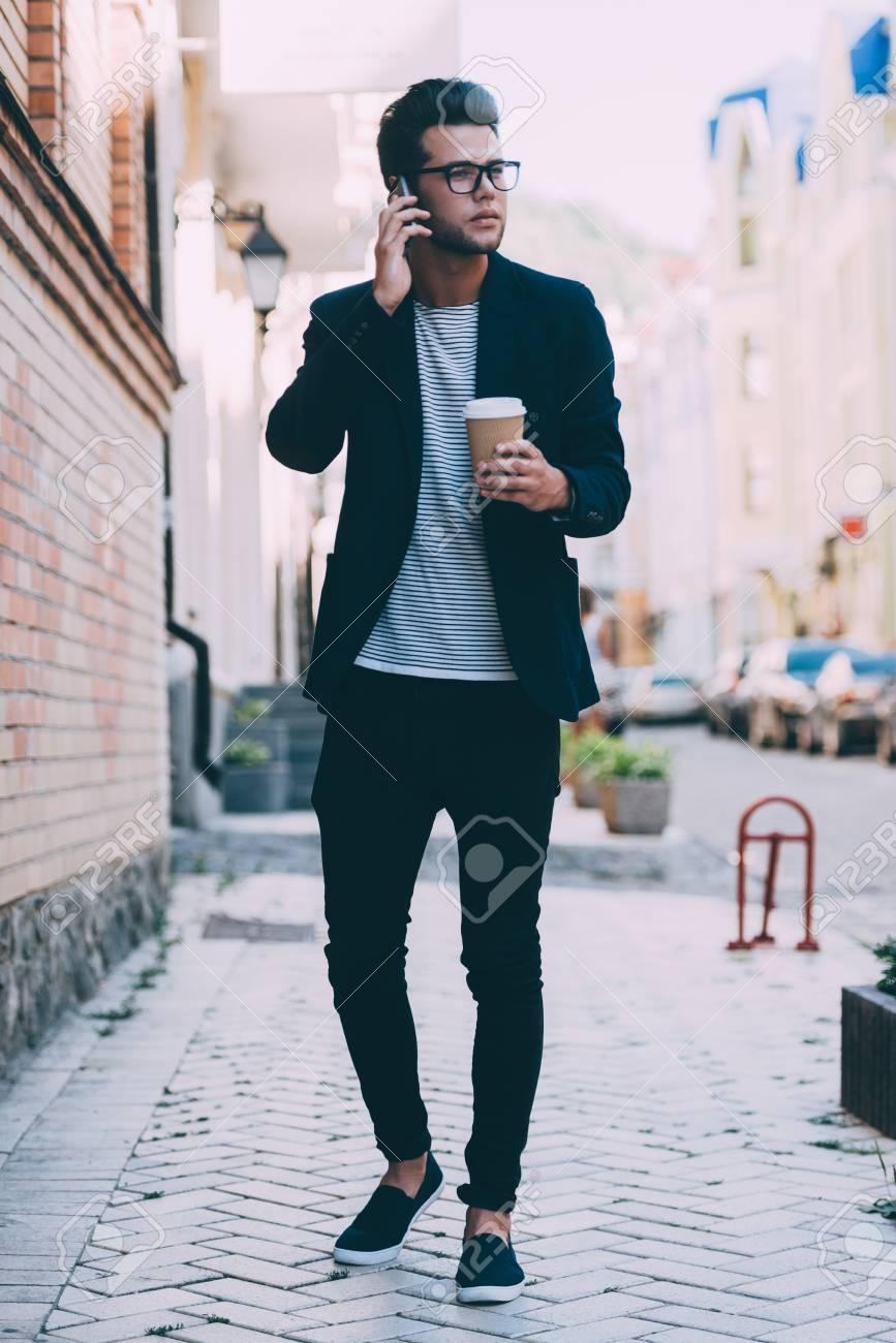 de341d3d7f0 Integral De Hombre Joven Y Guapo En Ropa De Sport Elegante Llevar Taza De  Café Y Hablando Por Teléfono Móvil Mientras Se Camina A Lo Largo De La ...