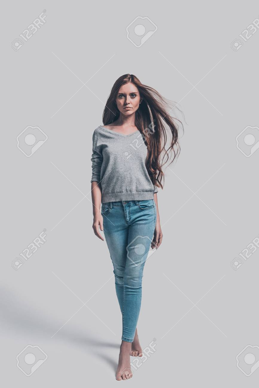 Confident and beautiful. Full length studio shot of attractive young woman in casual wear walking and looking at you - 65334581