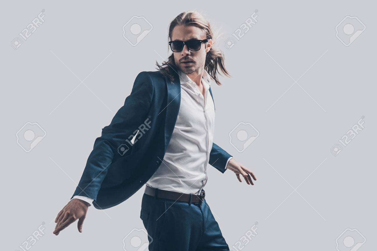 b832eae8d869 Stock Photo - Style in motion. Handsome young man in full suit and  sunglasses moving in front of grey background