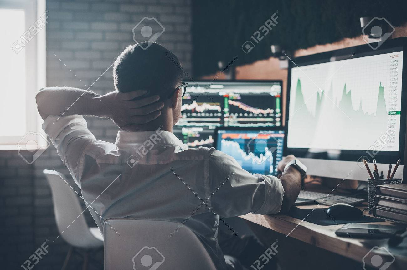 Thinking about new solutions. Rear view of young man in casual wear holding hand on the back of the head and working while sitting at the desk in creative office Banque d'images - 67275335