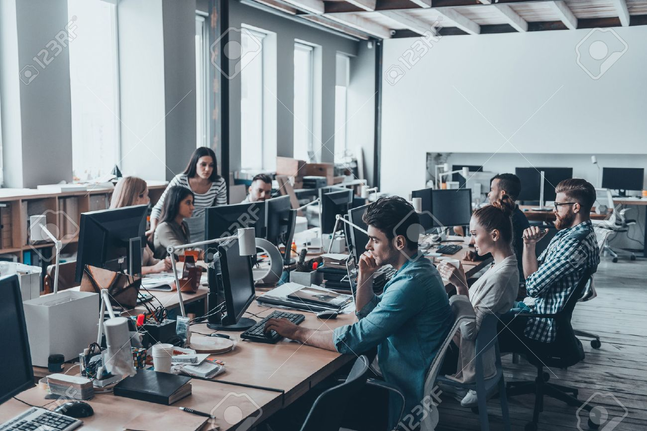 Busy working day. Group of young business people concentrating at their work while sitting at the large office desk in the office together Banque d'images - 71537725