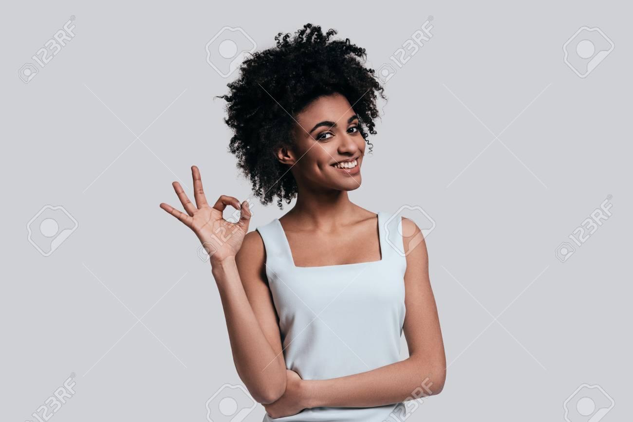 41b6b67cdc Tutto è perfetto. Giovane bella donna africana nell'abbigliamento casual  che gesturing e che esamina macchina fotografica mentre stando contro il ...