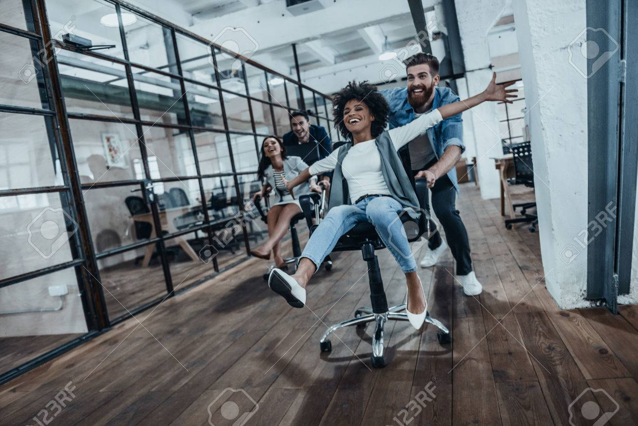We are the winners!  Four young cheerful business people in smart casual wear having fun while racing on office chairs and smiling Banque d'images - 73452853