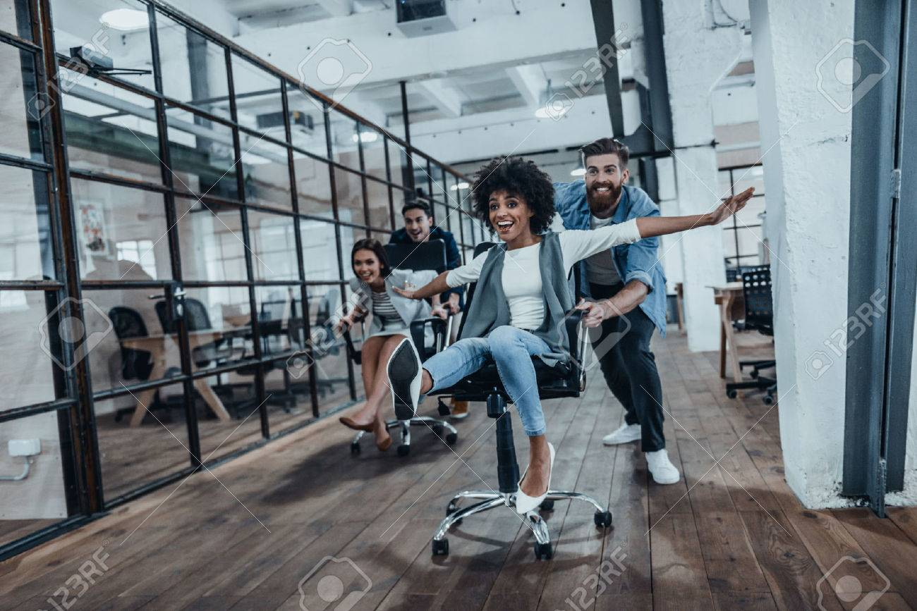 Office fun. Four young cheerful business people in smart casual wear having fun while racing on office chairs and smiling Stock Photo - 73530152