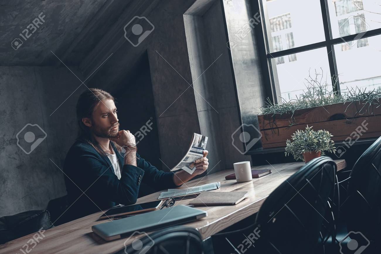 2853100a847 Stock Photo - What is new in the world  Handsome young man in smart casual  wear reading a newspaper while sitting at his desk in office