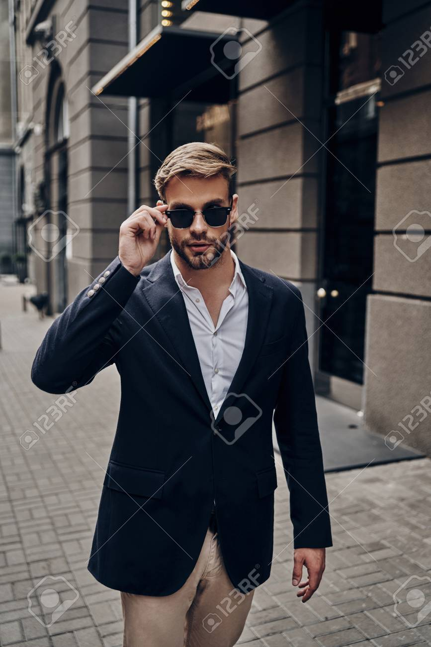 3df8ece559 In his own style. Handsome young man in smart casual wear adjusting his  eyewear while