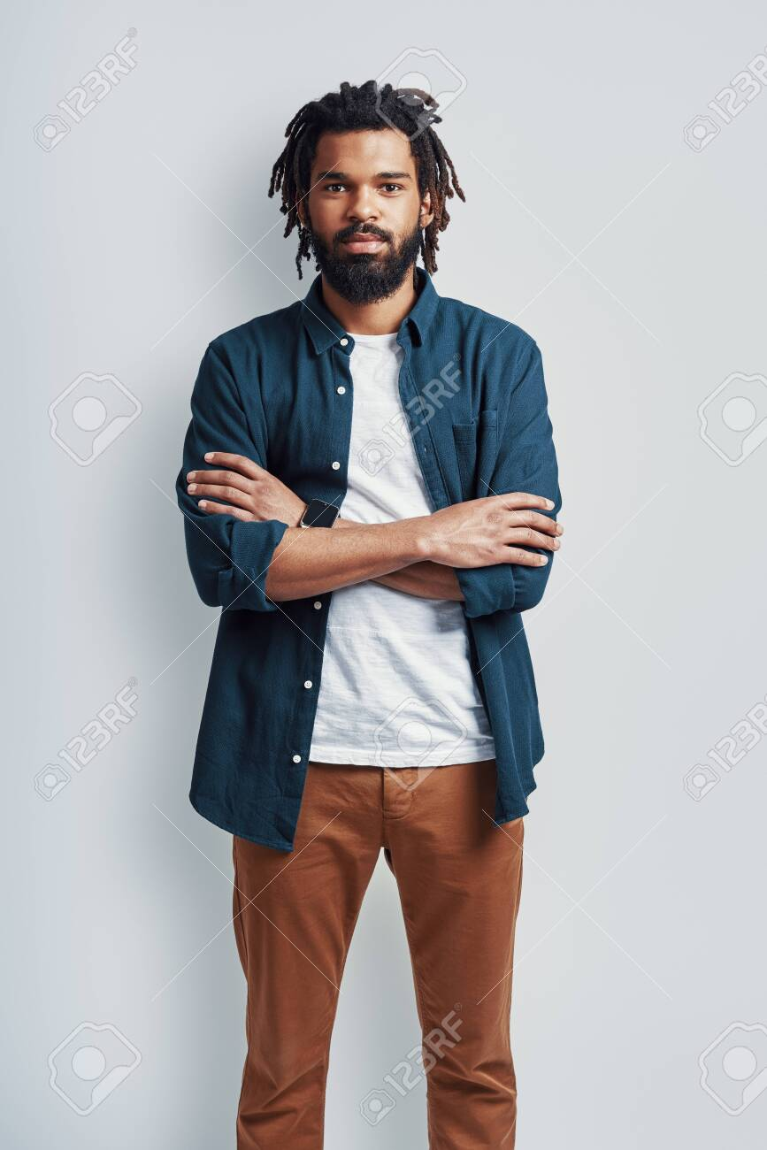 Thoughtful young African man in casual wear looking at camera and keeping arms crossed while standing against grey background - 150559335
