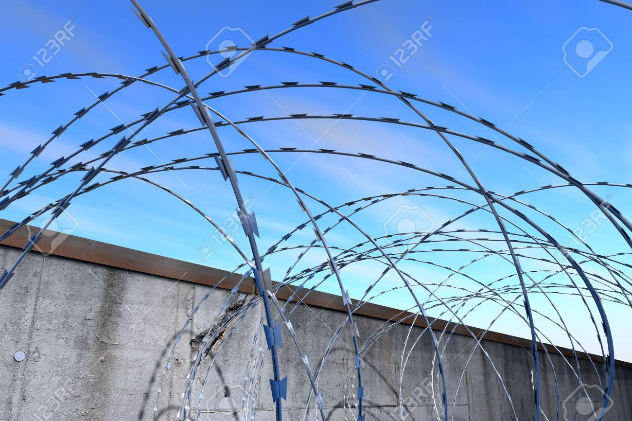 Barbed wire - Barbed wire at a grey concrete wall under a blue sky Stock Photo - 7718034