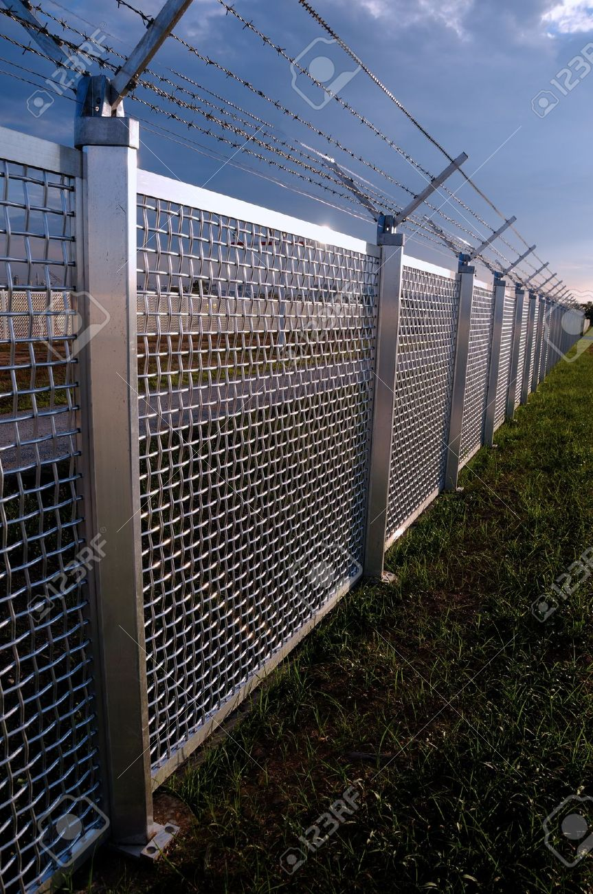 metal fence part of a metal grid fence with barbed wire at the