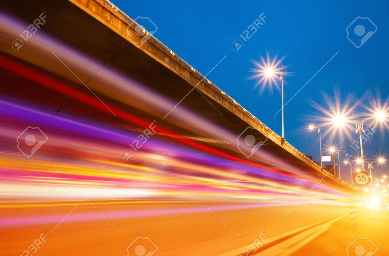 High speed traffic and blurred light trails under the overpass at night scene - 12042694