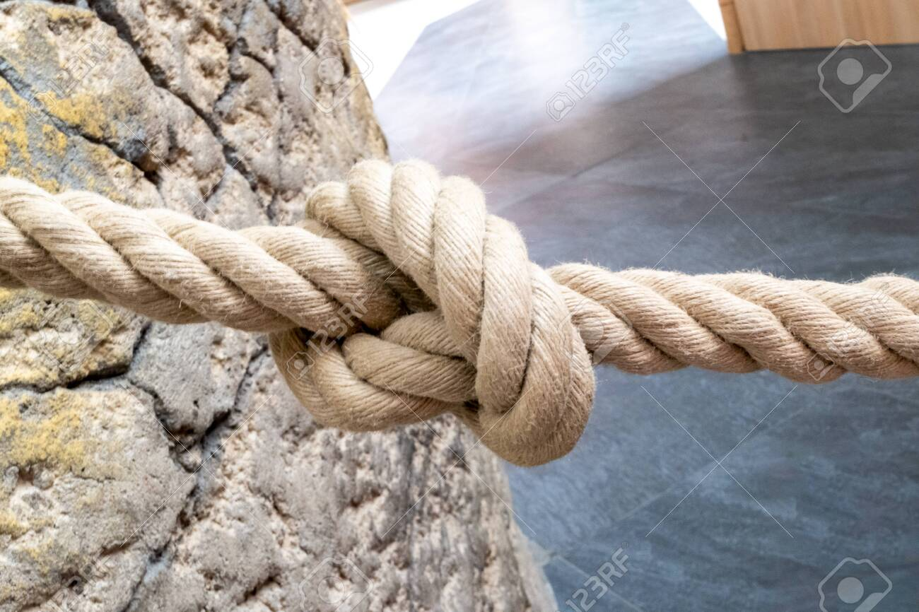 A rope made of natural fibre, which is used as a barrier rope, tied to a natural stone wall with a knot in the middle. - 149659167