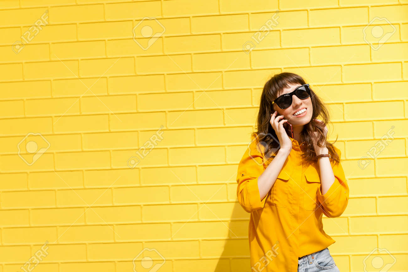 Girl on the phone was told the happy news Girl in yellow shirt against the yellow wall, talking on the phone. Copy space - 152568935