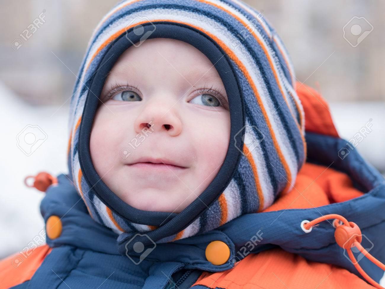 2ec3e542838ef Attrayant petit garçon jouant avec la première neige. Il sourit et regarde  bonhomme de neige