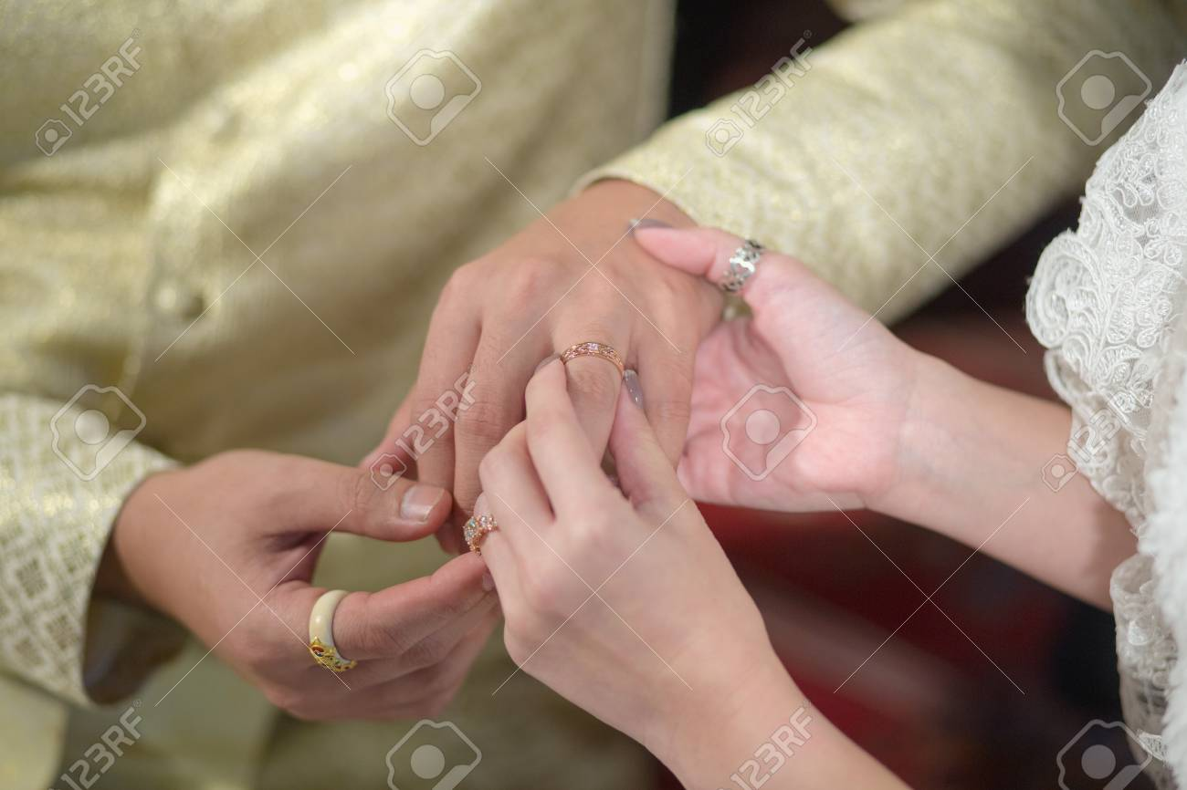 Thai Bride Wearing Wedding Ring For Her Groom Hand In Thai Wedding ...