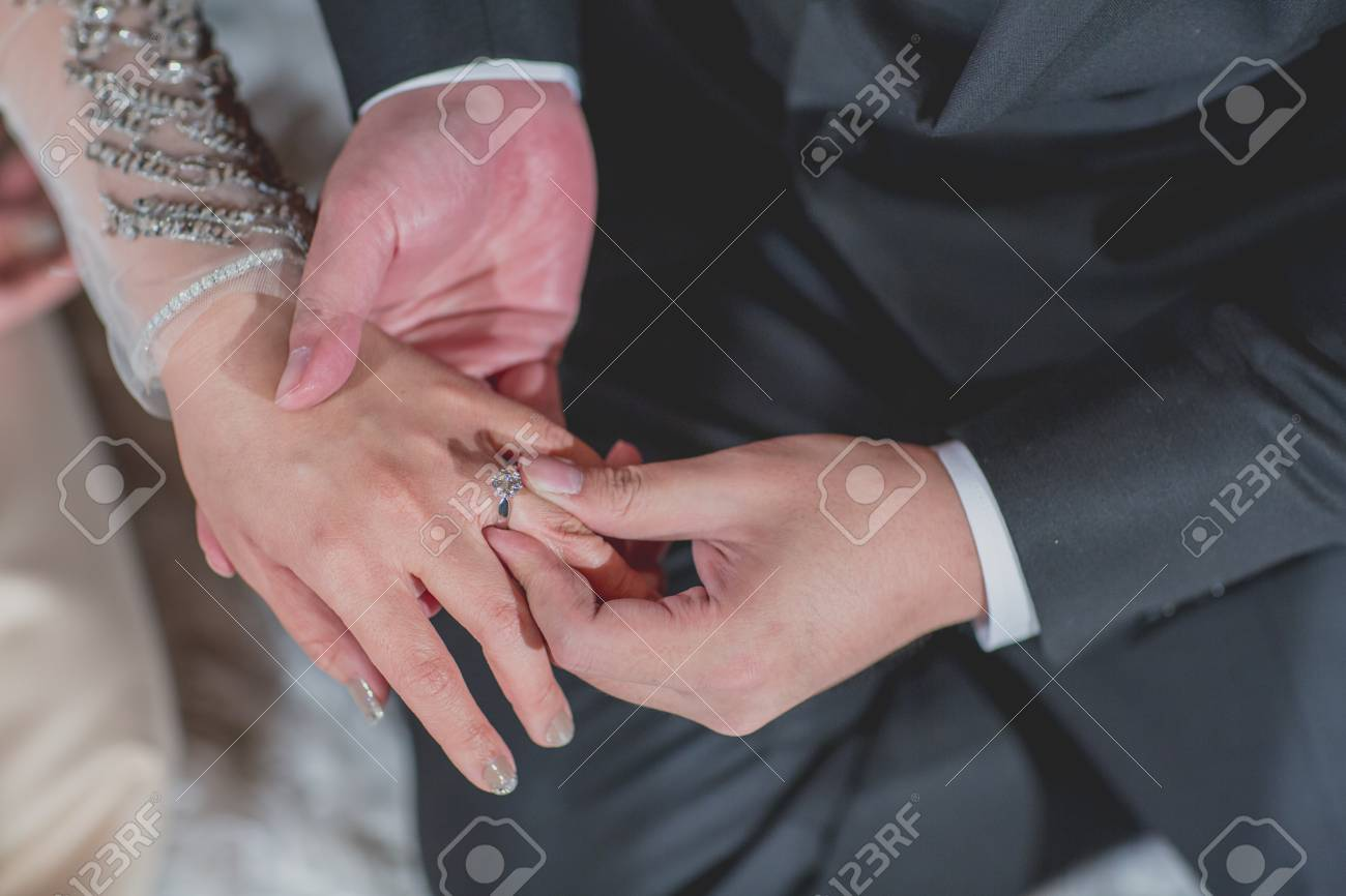 Groom\'s Hand Putting A Wedding Ring On The Bride\'s Finger. Stock ...