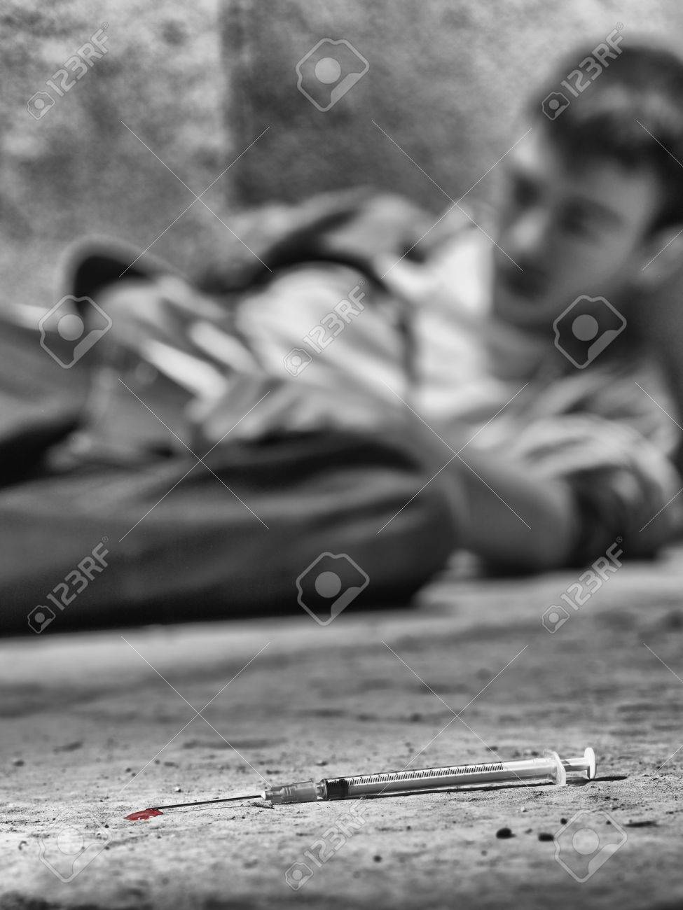 Young drug addict with a syringe in foreground - 38156369