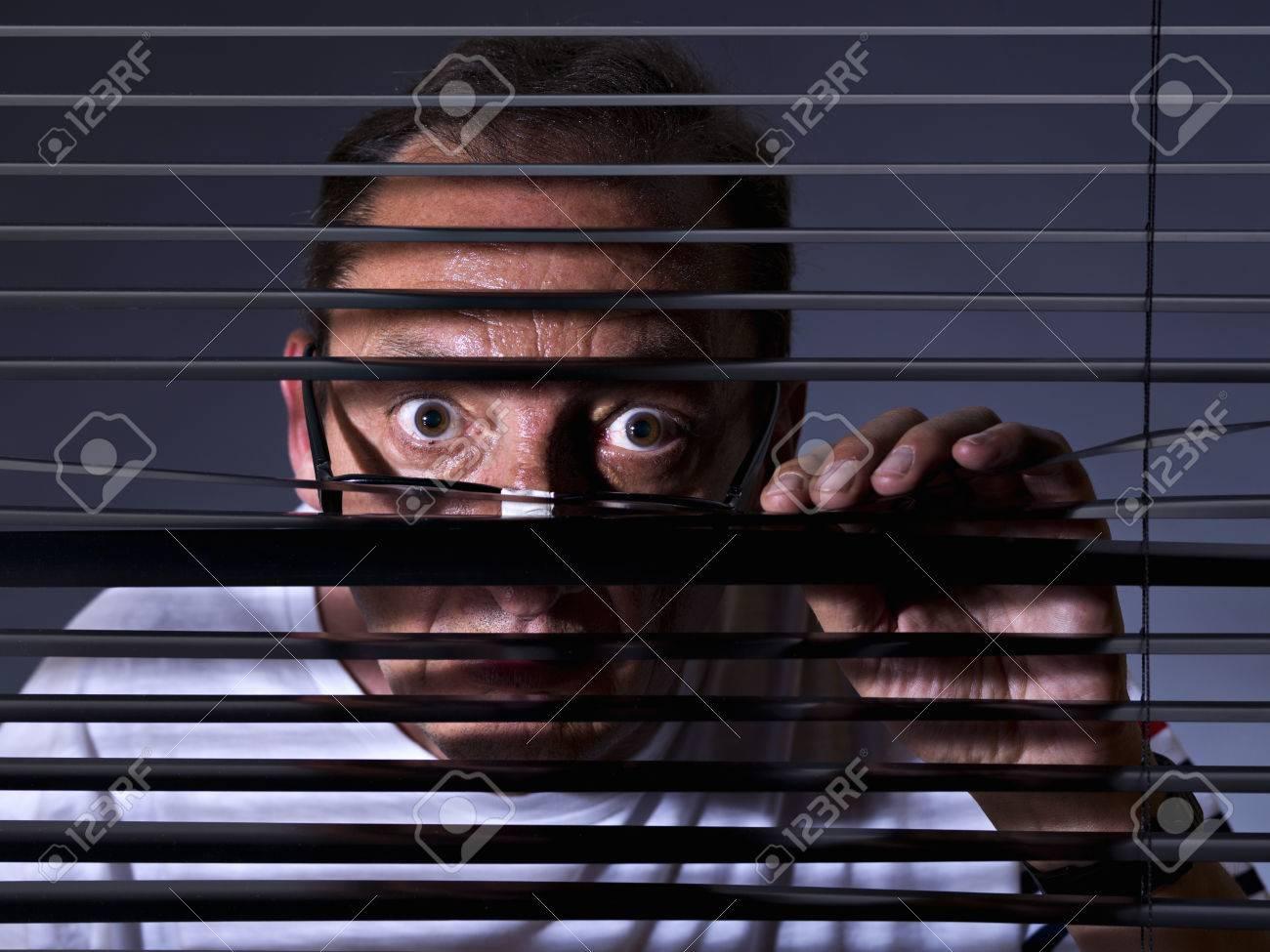 Vicious man looking sideways through venetian blind - 38156718