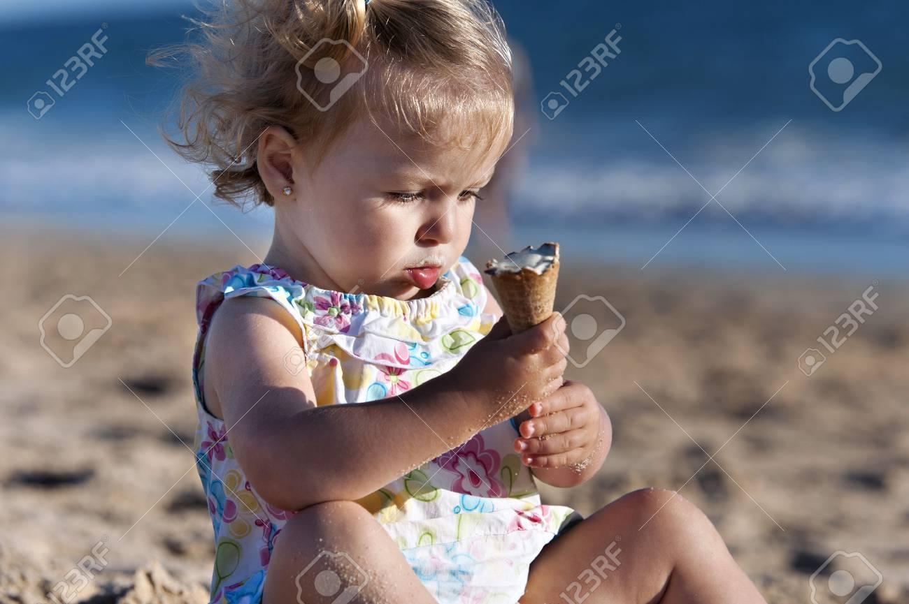 Small girl taking an ice cream in the beach - 38160257