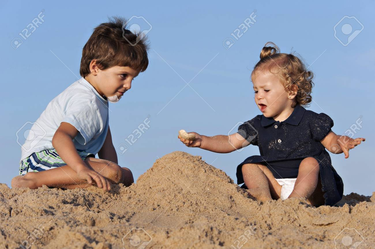 Two children have fun on the beach playing with the sand - 38161182