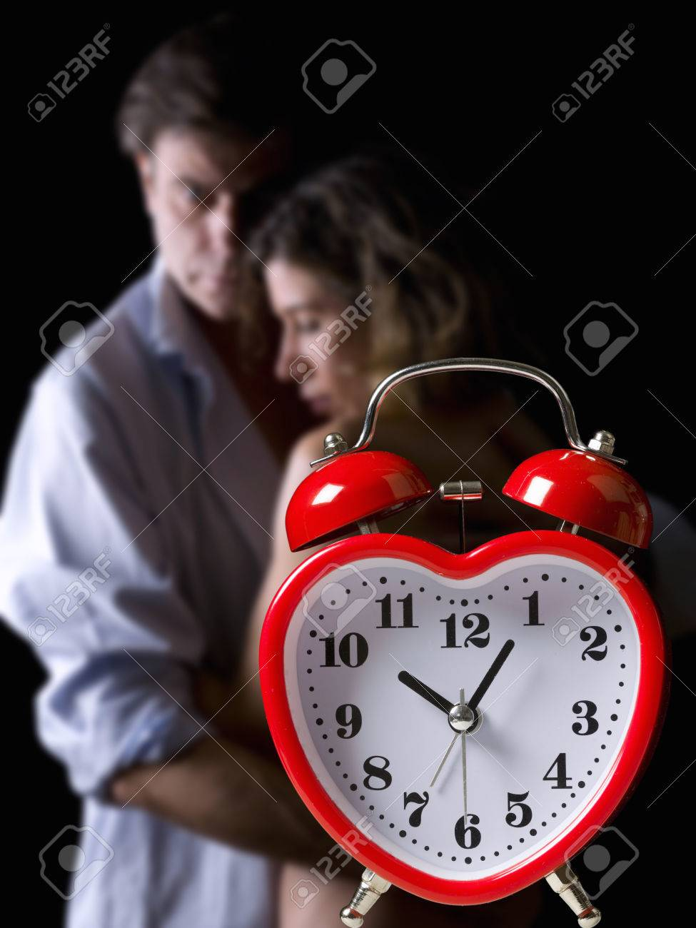 Clock and an embracing couple in the background - 38161380