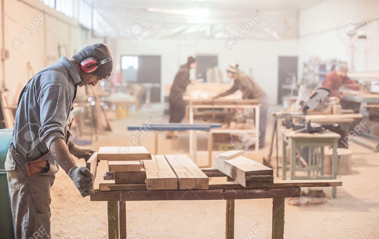Man doing woodwork in carpentry. Carpenter work on wood plank in workshop - 52528422