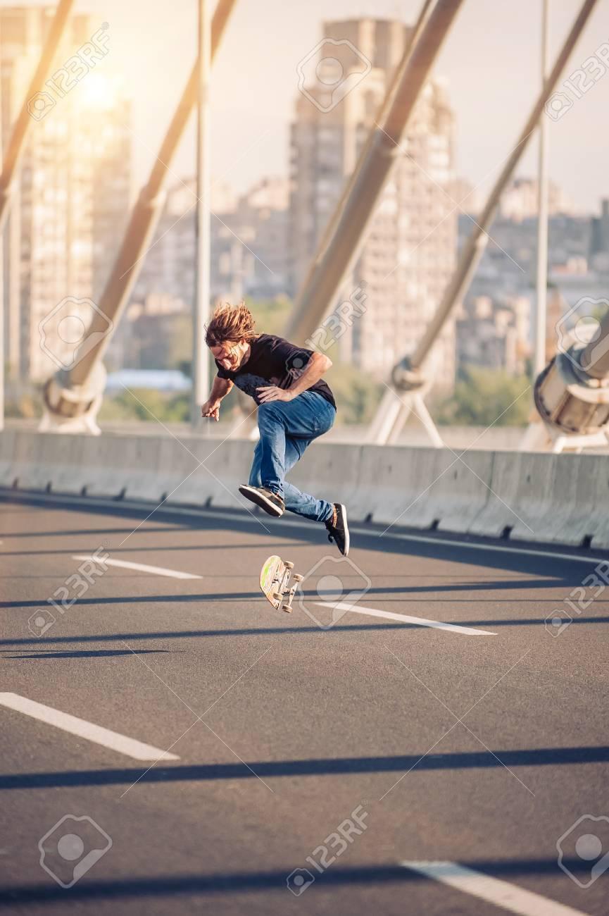 skater doing tricks and jumping on the street highway bridge