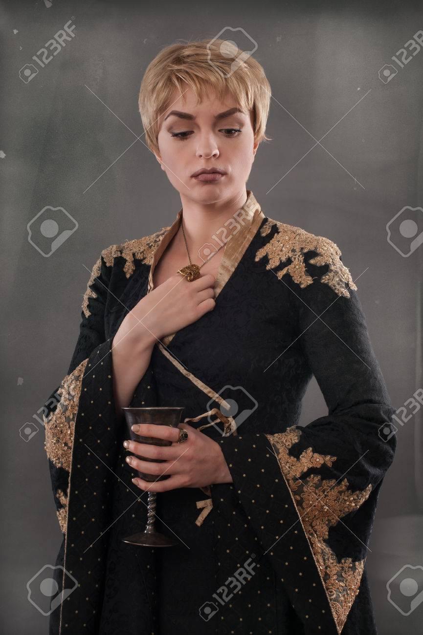 renaissance mode frau mit wein hält becher. klassische schönheit in einem  schicken renaissance kleid und eine passende frisur