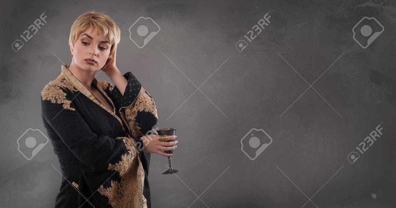 Renaissance fashion woman holding goblet with wine  Classical