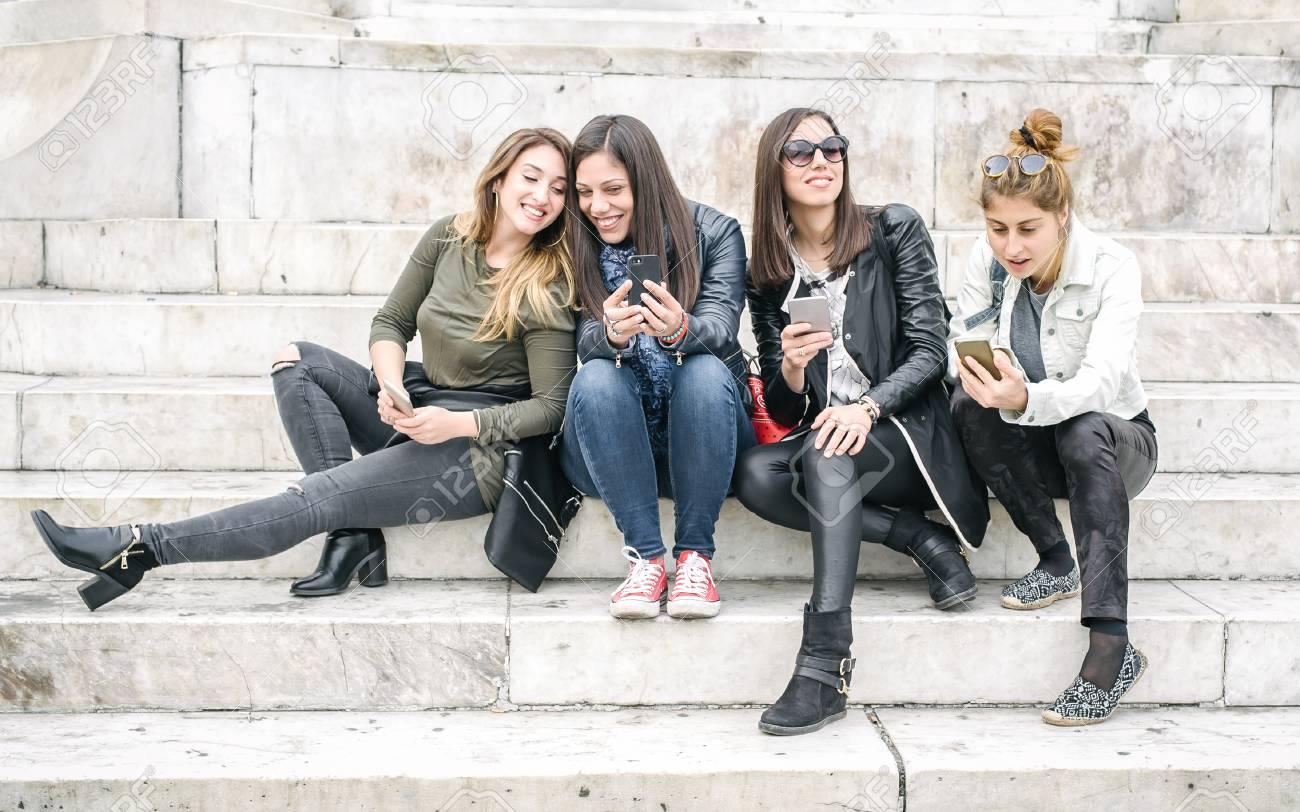 Cuatro Amigas Felices Que Miran Medios Sociales De Internet En