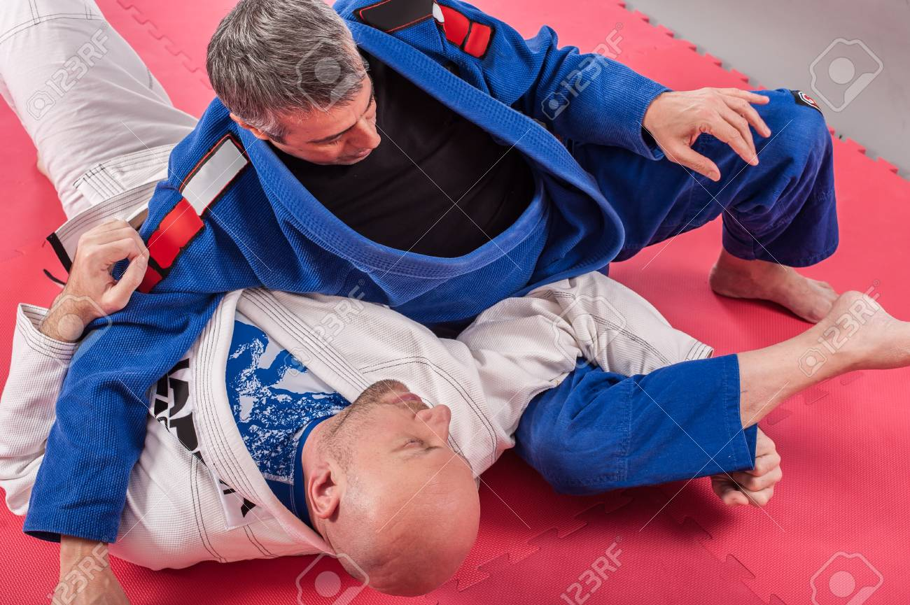Kapap and brazilian jiu jitsu instructor in traditional kimono demonstrates  ground fighting arm lock techniques with