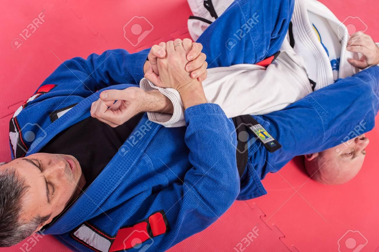 Brazilian jiu jitsu training in traditional kimono. Parterre and ground  lock techniques Stock Photo -