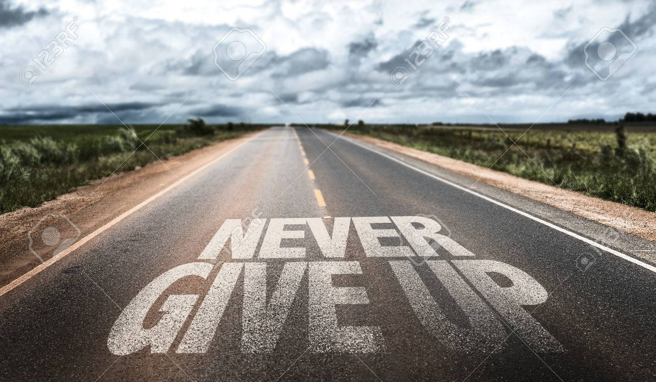 Never give up written on the road - 61112173