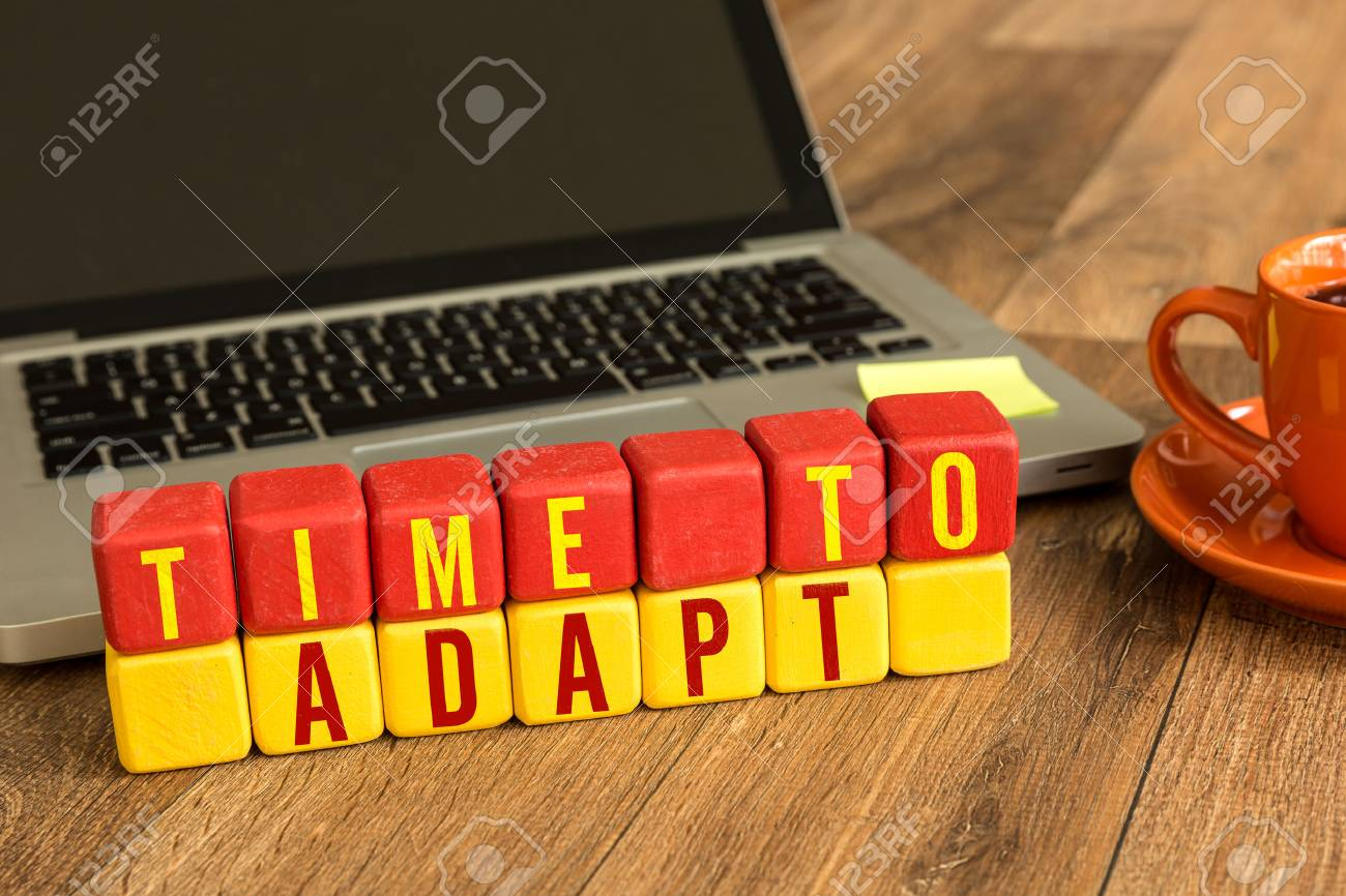 Time to adapt written on a wooden cube with laptop background - 64663346