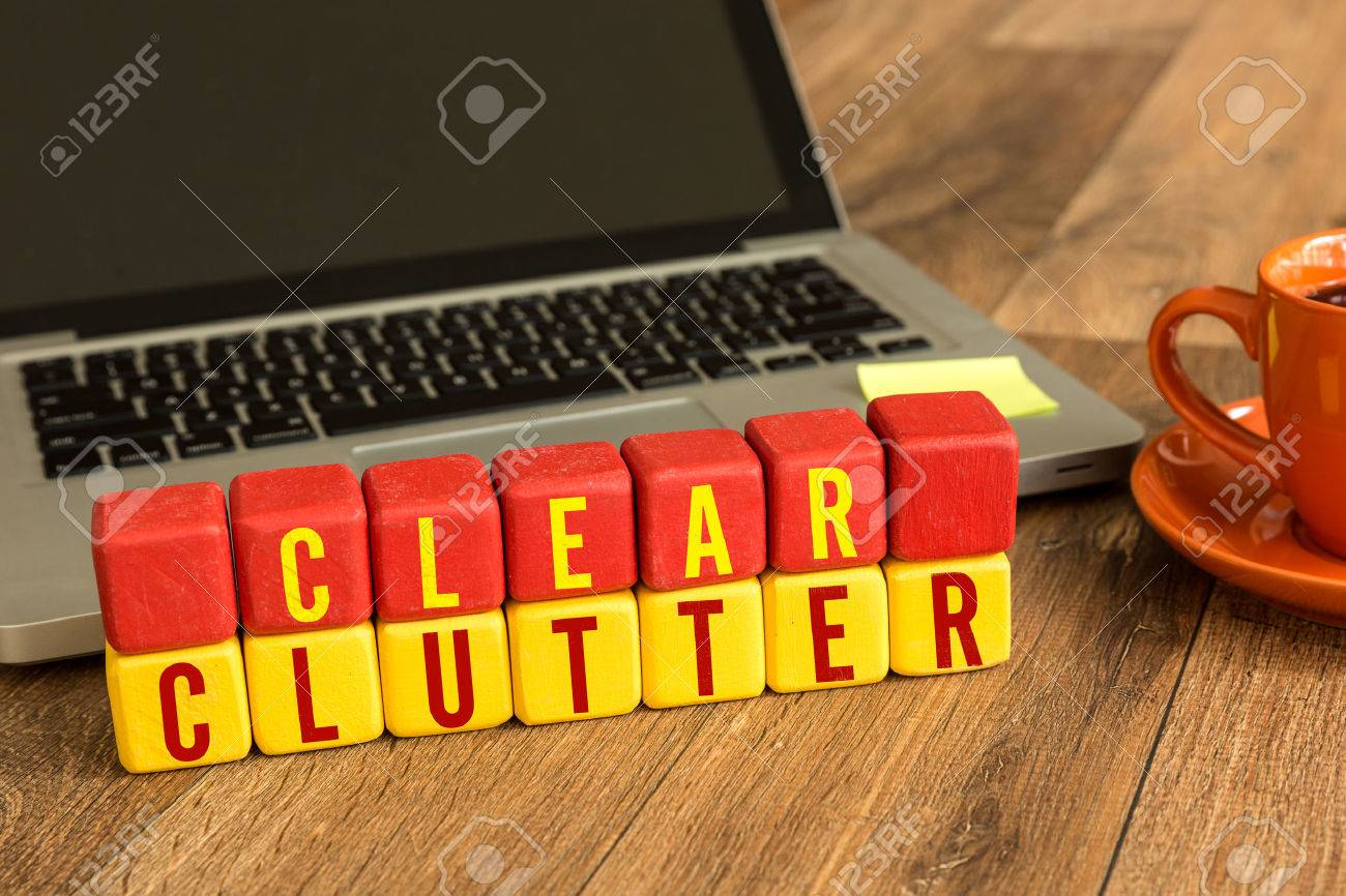 Clear clutter written on a wooden cube with laptop background - 64665543