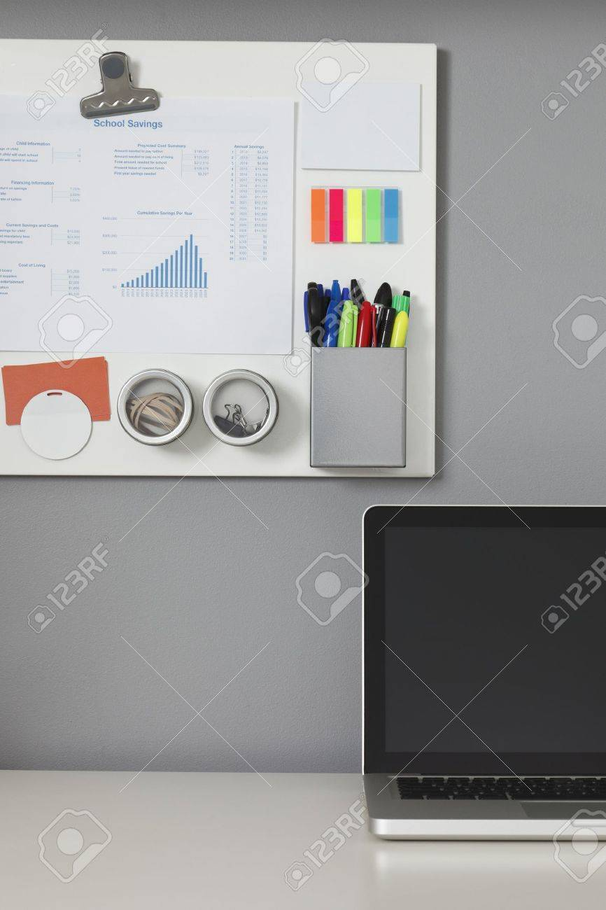 White office desk, laptop computer and a white magnetic board on a gray wall Stock Photo - 9633564
