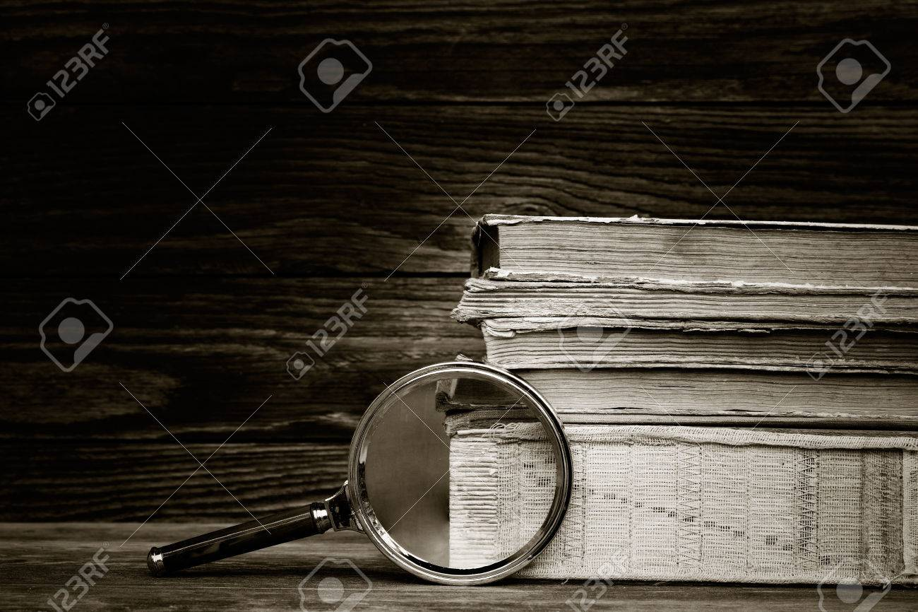 black and white photo. a pile of old books and magnifier on wooden background. the concept of the research, the study. with space for text - 56372426