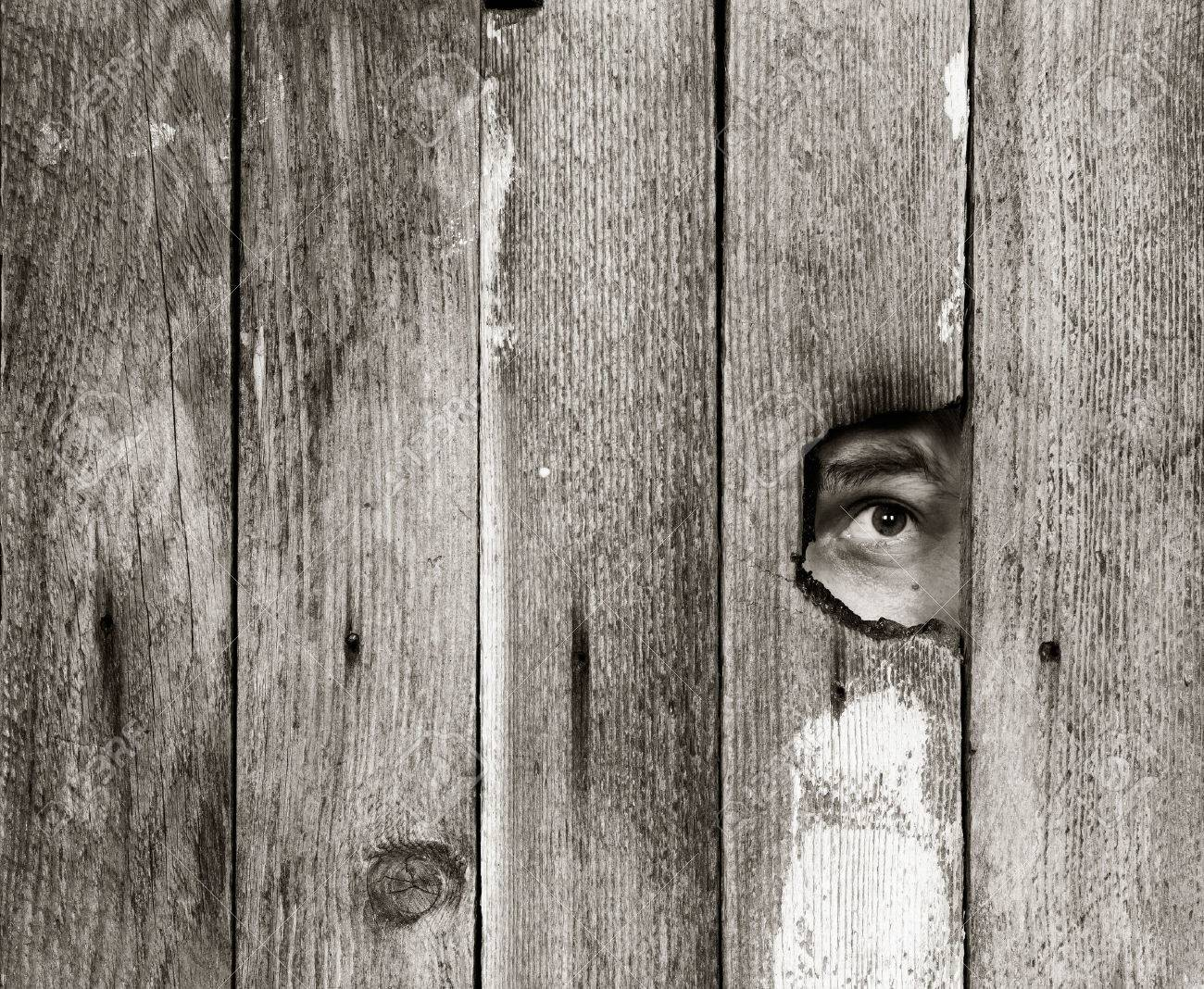 the eyes of a man spying through a hole in an old wooden fence. with space for posting information. black and white photo - 56429534