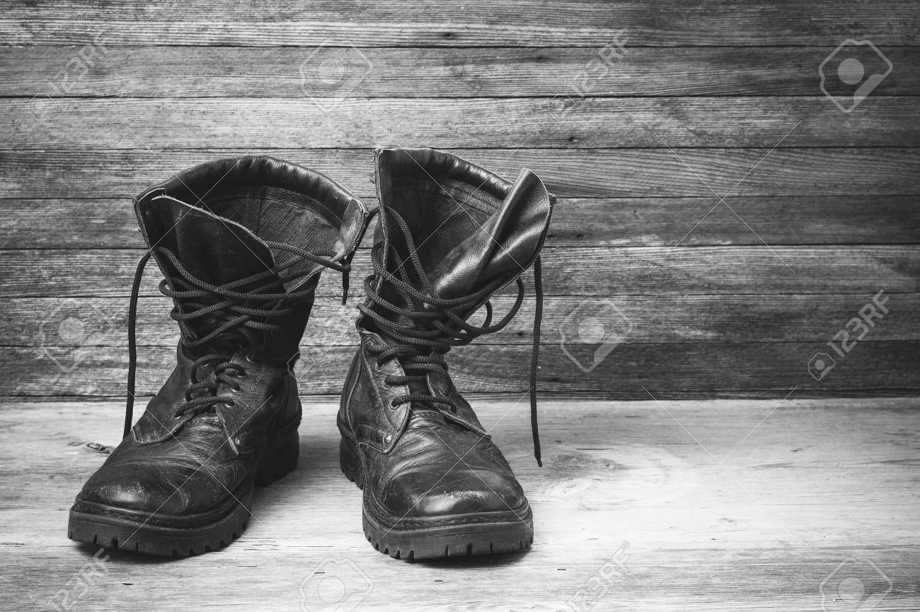 古い革ブラック メンズ靴足首ブーツ正面クローズ アップ木製の背景を黒と白の写真、あなたのテキストのためのスペース