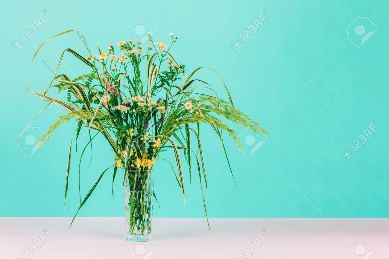 summer bouquet of green herbs and chamomile flowers in a gl.. on
