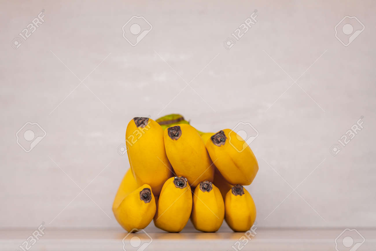 a bunch of yellow ripe bananas on a gray background close-up - 165439636