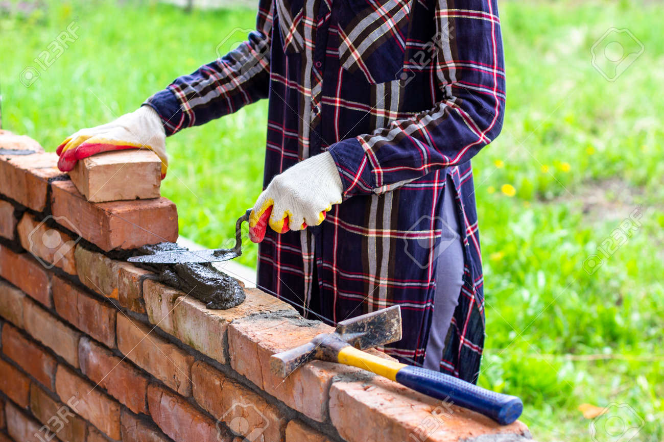 a young female bricklayer lays out cement mortar for laying bricks with a trowel on a brick wall - 169308579
