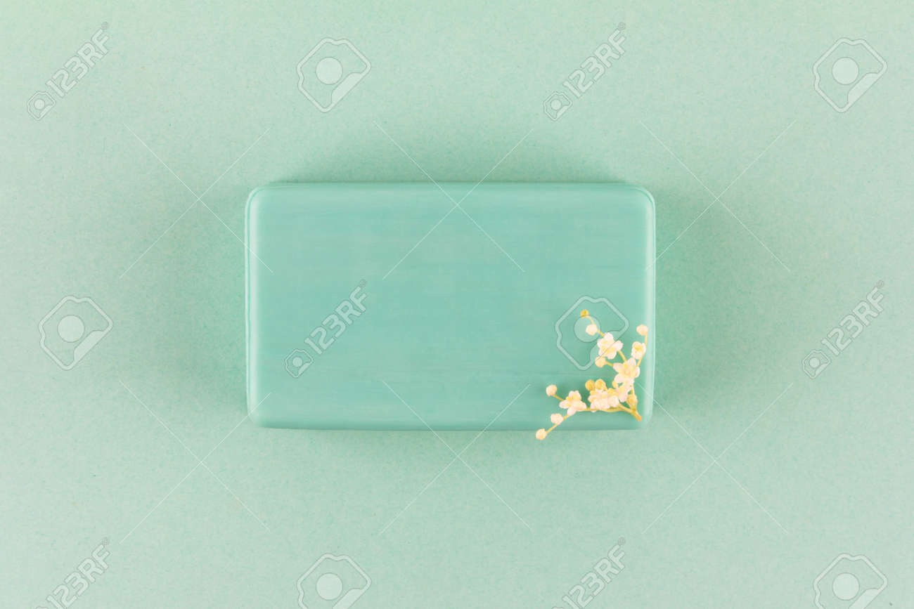 handmade soap bar with small white flowers on a green background top view - 169308571