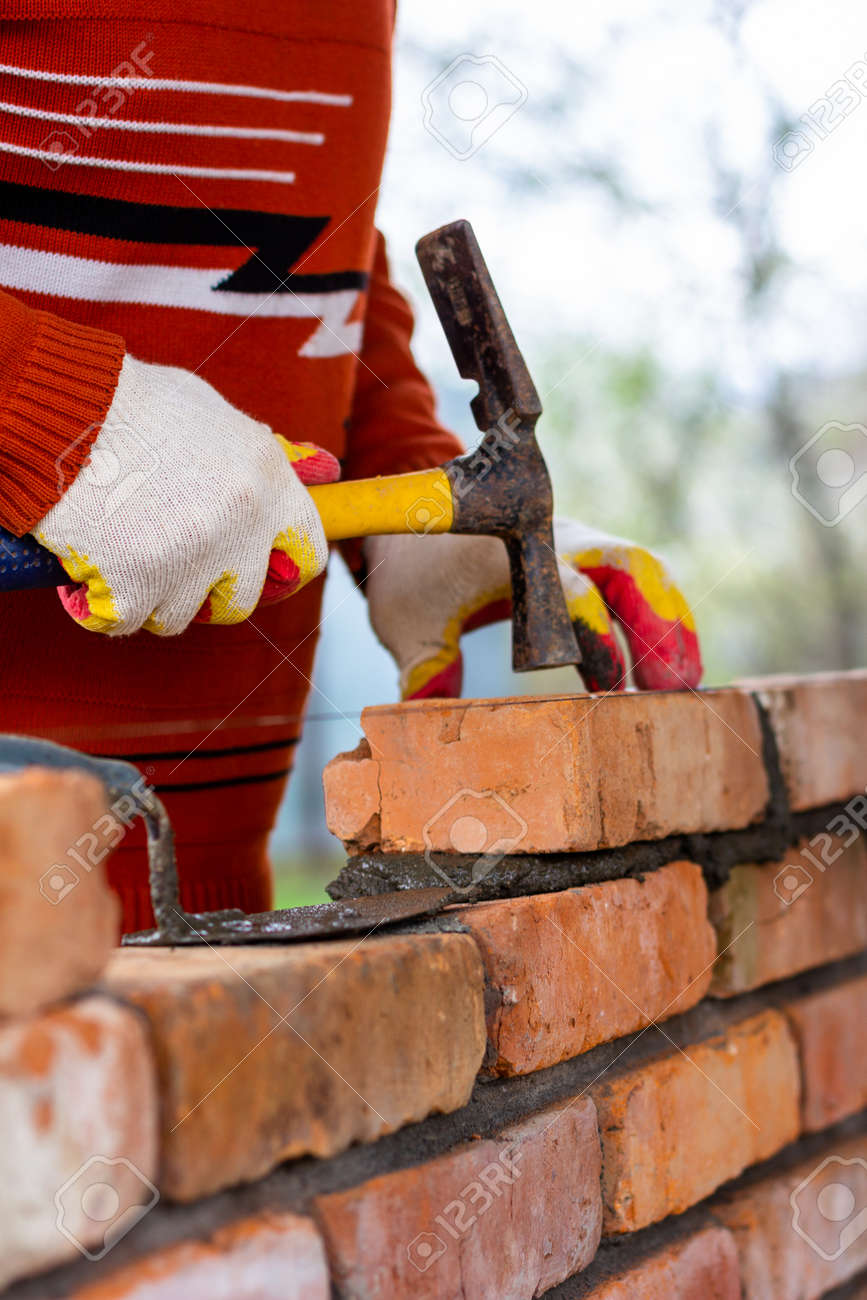 a man builds a brick wall, puts a brick on a cement-sand mortar, tapping a brick with a hammer - 170686167