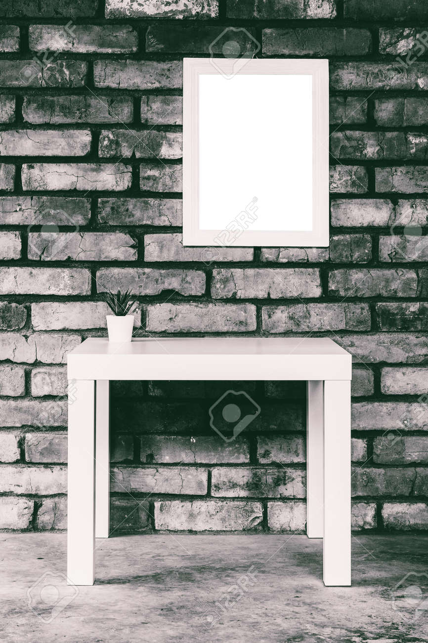minimalistic loft-style interior with a white table, mock up white picture frame or photo frame on a brick wall, black and white photo - 171894971