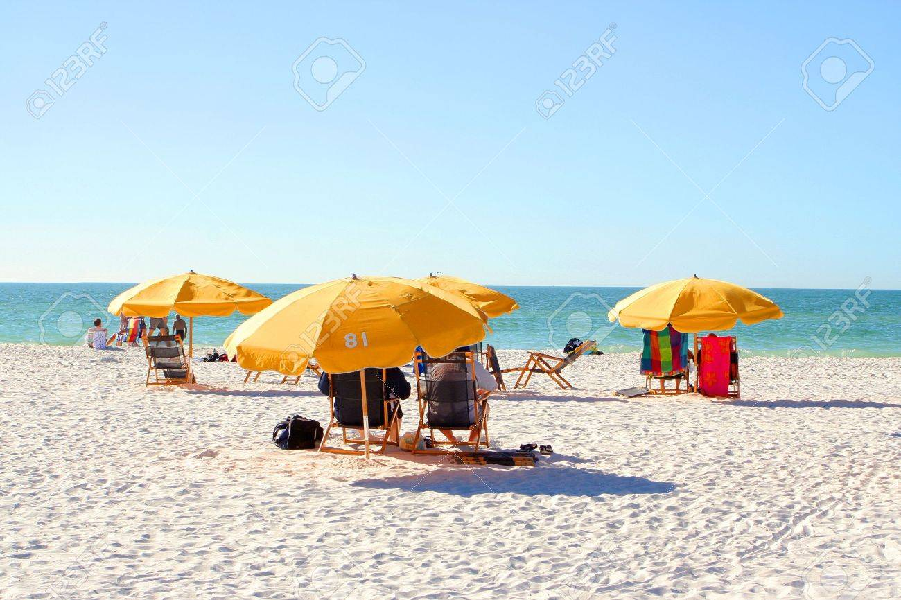 Beach With People Relaxing On Chairs Under Umbrellas In Clearwater Florida Usa