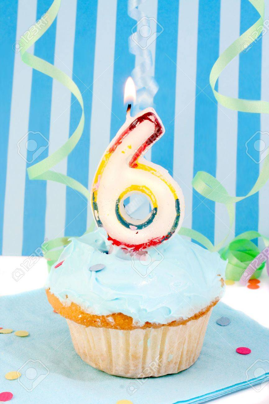 boy's sixth birthday cupcake with blue frosting and  decorative background Stock Photo - 3479700