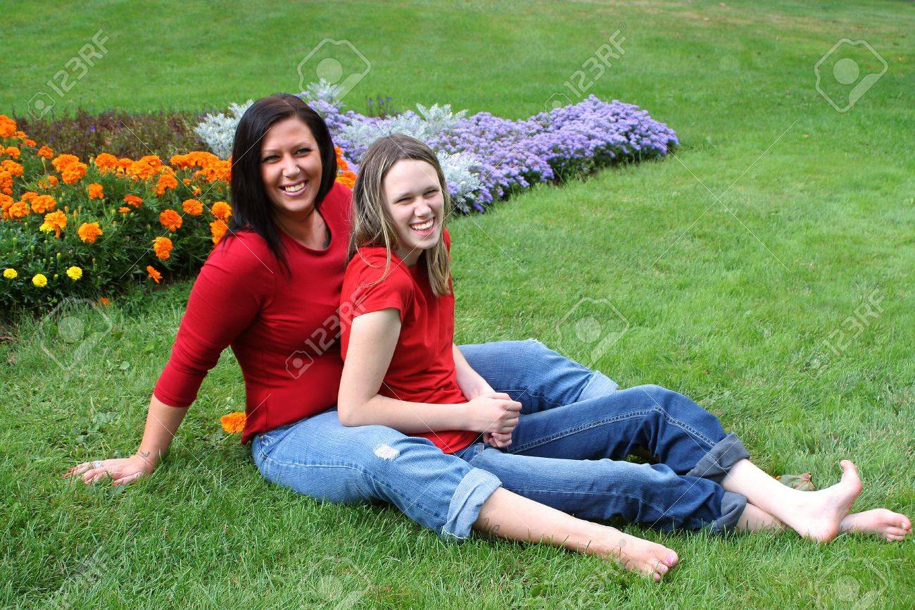 beautiful barefoot mother and daughter sitting on the grass with flowers in the background Stock Photo - 3519933