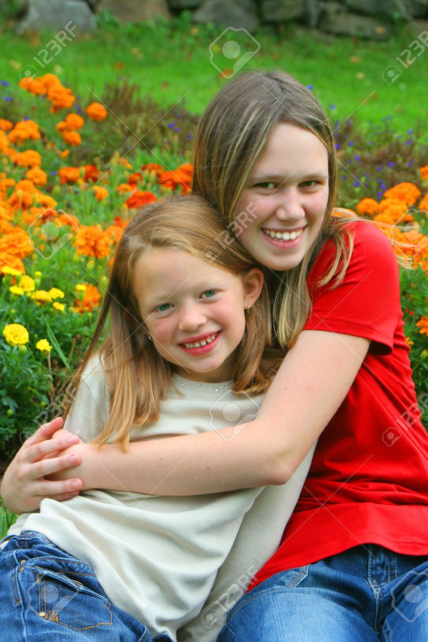 youngster girls Stock Photo - two young pretty girls that could be sisters, or cousins or a babysitter hanging out with the youngster